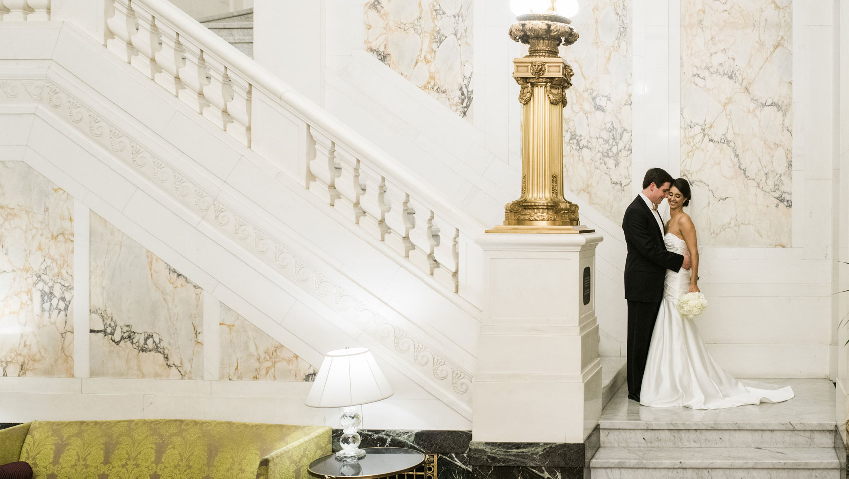 Courtney & Steve pose for a wedding portrait at the foot of the grand marble staircase at Kimpton Hotel Monaco Baltimore.