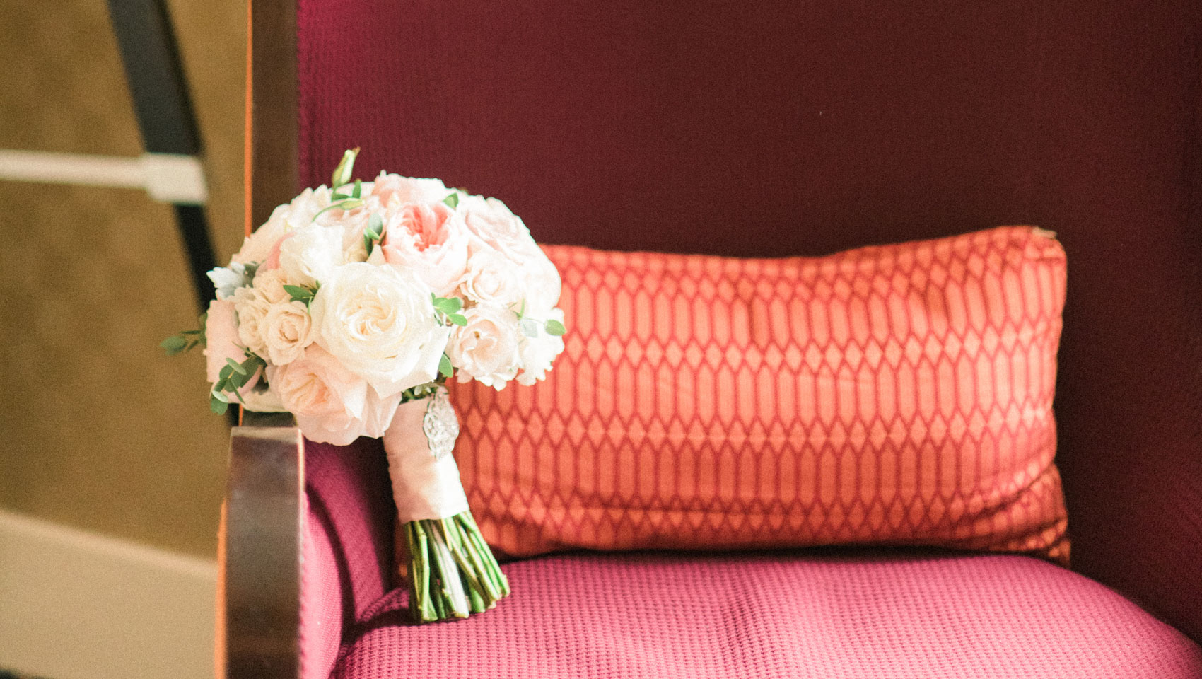 A bride's wedding bouquet rests on the arm of the suite's seating area.
